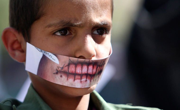Sana'a, Yemen: A boy wears a paper mask to depict silence