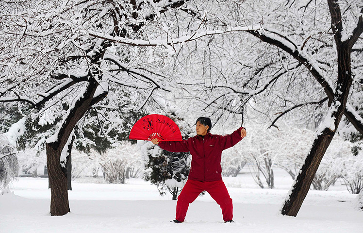 Shenyang, China: A woman practices tai chi with a fan after a snowfall