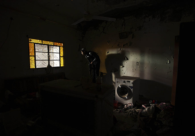 A Free Syrian Army fighter takes position inside a house in Deir al-Zor