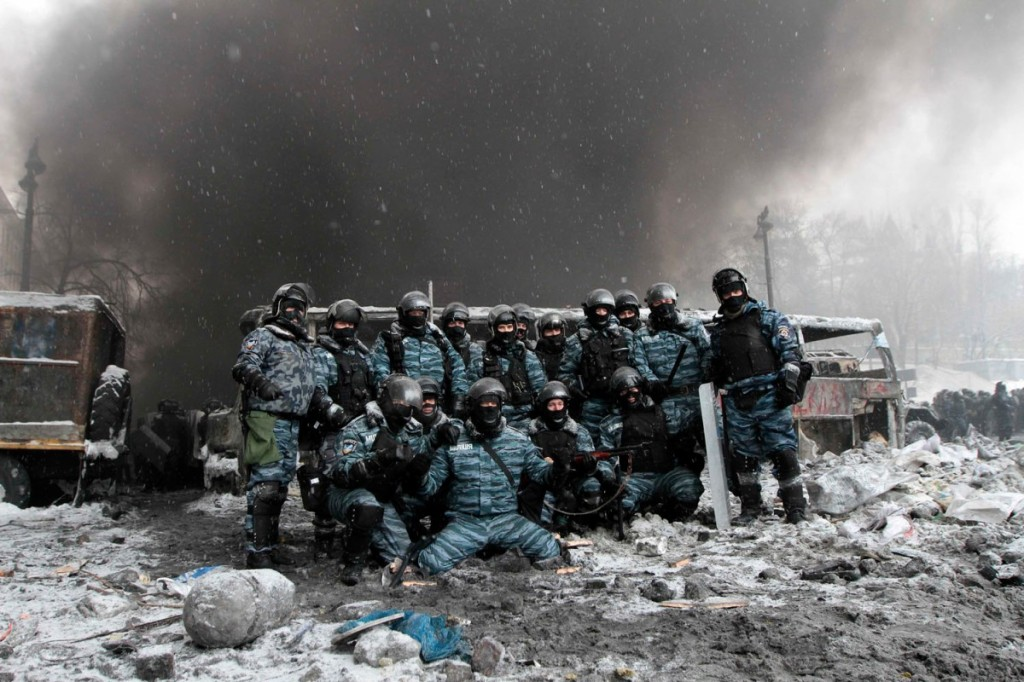 Riot police officers pose for a picture near burnt vehicles as smoke rises in the background during clashes with pro-European protesters in Kiev