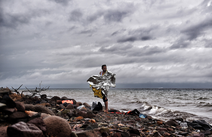 A man stands on the shore as refugees and migrants arrive on the Greek Lesbos island after crossing the Aegean Sea from Turkey on October 22, 2015. An EU scheme to relocate asylum seekers from overstretched Italy and Greece could grind to a halt just two weeks after it began if member states fail to meet their obligations, an EU source said. AFP PHOTO / ARIS MESSINIS (Photo credit should read ARIS MESSINIS/AFP/Getty Images)